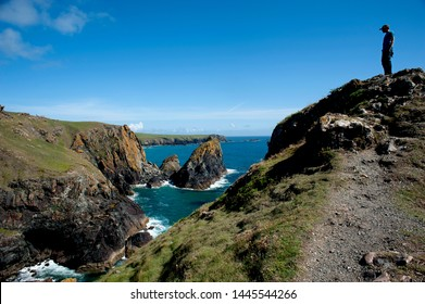Kynance Cove, Cornwall, England, July 2019. A walker stands on a headland above the dramatic coastline at the popular holiday destination of Kynance Cove in Cornwall.