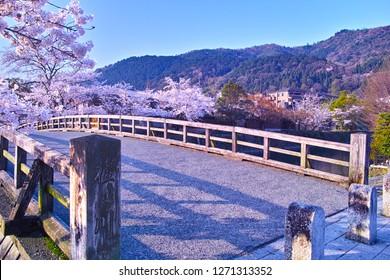 "Kyoto Arashiyama where spring cherry blossoms, Nakanoshima bridge hanging on Katsura river. In the lower left corner of the photo, the name of ""Katsura river"" kanji is engraved."