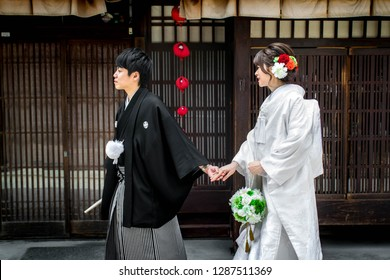 Kyoto, Kyoto / Japan - 05 12 2018: A young happy Japanese couple in traditional Japanese wedding attire, on their way to get married in the old part of Kyoto.