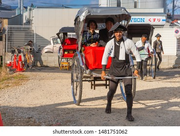 Kyoto, Japan - 17 Nov 2018: Japanese man, the rickshaw with tourists leaves the parking lot for carts in Kyoto. Rickshaws were part of traditional transportation and culture in medieval Japan.