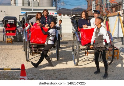 Kyoto, Japan - 17 Nov 2018: Japanese men, the rickshaws with tourists at the parking lot for carts in Kyoto. Rickshaws were part of traditional transportation and culture in medieval Japan.