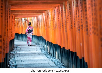 KYOTO, JAPAN - 2016  November 21 : Two geishas wearing traditional japanese kimono among red wooden Tori Gate at Fushimi Inari Shrine in Kyoto, Japan. Fushimi Inari Shrine one of famous landmarks.