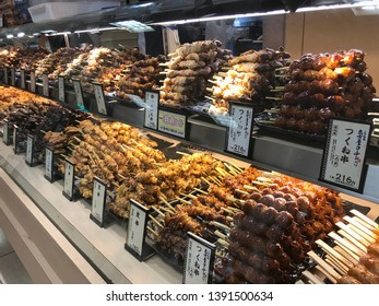 Kyoto, Japan - 2019-04-12 : Piles of Variety of meats grilled on a bamboo stick in different flavors knows as yakitori ready for sale at a busy market in downtown Kyoto, Japan