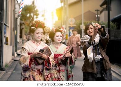 Kyoto, Japan : 21-November-2017 : Tourist is enjoy selfie with Japanese woman Geisha on the street in Kyoto, Japan.