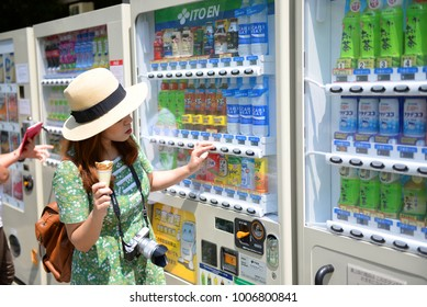 Kyoto, Japan 23-May-2016 : Asian woman tourist is selecting soft drink at soft drink vending machine in Kyoto, Japan.