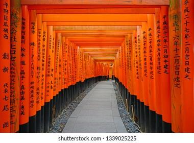 KYOTO, JAPAN -24 FEB 2019- View of red tori gates with columns at the Fushimi Inari Taisha shrine, located at the base of the Inari mountain in Kyoto, Japan.