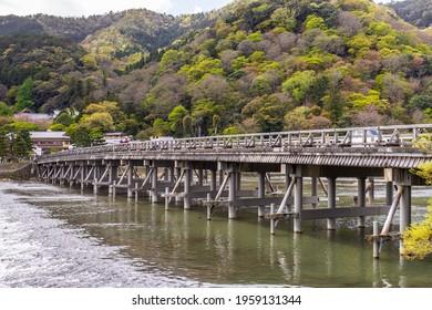 Kyoto, JAPAN - 5 Apr 2021 : Togetsukyo Bridge, a bridge across the Katsura River which flows leisurely through Saga Arashiyama area, in cloudy day. Pedestrians, tourists and cars in image
