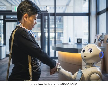 KYOTO, JAPAN - APR 14, 2017 : Pepper Robot Greeting shake hand with Asian tourist Humanoid Technology