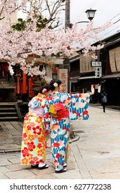 Kyoto, Japan - April 11, 2017: Two Japanese Women wearing Kimono taking Selfie Picture with Smart Phone with Cherry Blossom in Background in Kyoto Japan. Kyoto is an ancient city in central Japan.