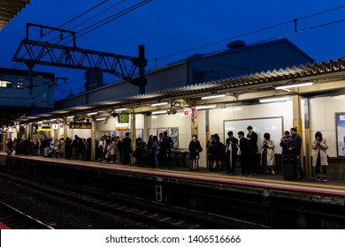 Kyoto, Japan - April 11, 2019: Train station platform in tofukuji with people waiting for shinkansen and salaryman businessmen on commute in dark evening with blue sky