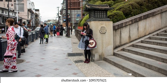 Kyoto / Japan - April 12, 2018: Japanese woman in loli dress at the entrance to Shinto Temple of Heian on a festive day, Japanese in kimono