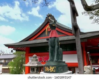 KYOTO, JAPAN - APRIL, 16, 2018: fox statue holding a rice sheaf at fushimi inari temple in kyoto