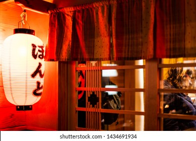 Kyoto, Japan - April 16, 2019: Pontocho alley sign on red lantern in hiragarna in district street at night with illuminated lamp and izakaya restaurant entrance exterior