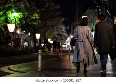 Kyoto, Japan - April 16, 2019: Couple holding hands walking on Kiyamachi-dori street near Pontocho alley district at night with illuminated lanterns