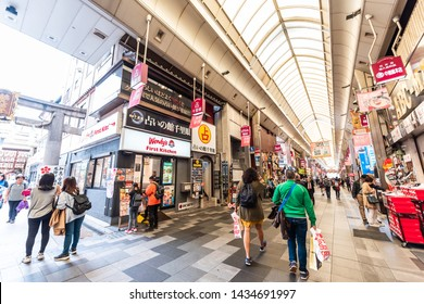 Kyoto, Japan - April 17, 2019: Many people shopping in Nishiki market street shops for food with stores signs for Wendy's