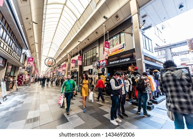 Kyoto, Japan - April 17, 2019: Many people shopping in Nishiki market shops for souvenirs with stores signs for American Lounge