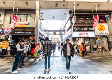 Kyoto, Japan - April 17, 2019: Many people shopping in Nishiki market street shops for food and souvenirs with stores signs for Wendy's and American Lounge