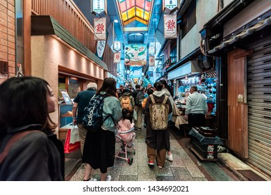 Kyoto, Japan - April 17, 2019: Many people shopping in covered Nishiki market arcade street shops for food and souvenirs
