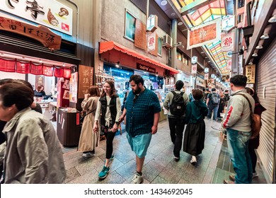 Kyoto, Japan - April 17, 2019: Many people couple shopping in Nishiki market arcade street shops for food and souvenirs