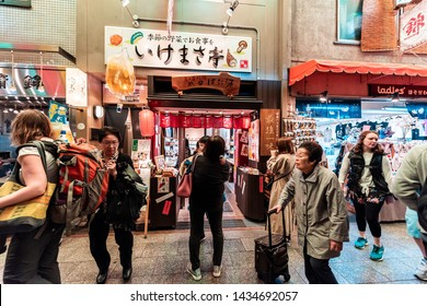 Kyoto, Japan - April 17, 2019: Many people shopping in Nishiki market arcade street shops for food and souvenirs