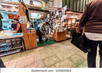 Kyoto, Japan - April 17, 2019: People shopping in Nishiki market street shops and man cleaning sweeping souvenir store for socks