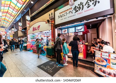 Kyoto, Japan - April 17, 2019: People shopping in Nishiki market street covered shops for groceries and tacos