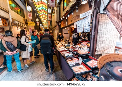 Kyoto, Japan - April 17, 2019: City street with people shopping in Nishiki market shops food vendor selling souvenirs rice crakers