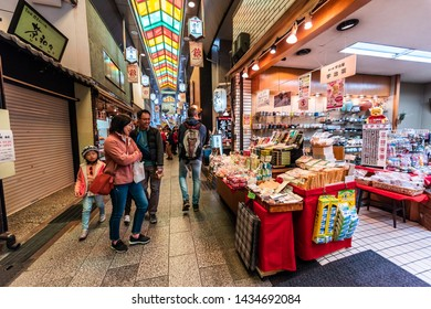 Kyoto, Japan - April 17, 2019: People shopping in Nishiki market arcade street covered shops looking at souvenirs