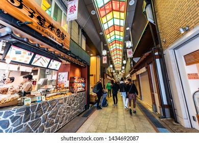 Kyoto, Japan - April 17, 2019: City street with people shopping in Nishiki market arcade covered shops restaurants and food vendors