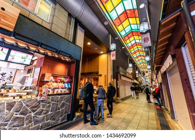 Kyoto, Japan - April 17, 2019: City with people shopping in Nishiki market arcade covered shops restaurants and food vendors