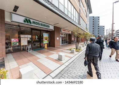 Kyoto, Japan - April 17, 2019: People walking near Nijo Station in morning by Mos Burger fast food restaurant wide angle view
