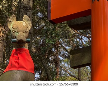 Kyoto, Japan - April 2019: Kitsune (fox) statue wearing a red bib and holding a scroll in it's mouth, Fushimi Inari Shrine, Kyoto, Japan. Inari is the god of rice.