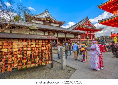 Kyoto, Japan - April 24, 2017: wooden plaques or Ema, bearing people's prayerspeople, women in kimonos takes selfie and red pagoda inside Kiyomizu-dera, one of the most celebrated temples of Japan.