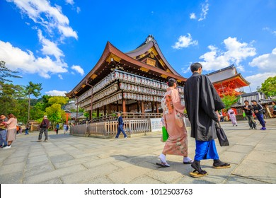 Kyoto, Japan - April 24, 2017:japanese couple in traditional clothes walking near ancient wooden pavilion of main hall decorated with paper lanterns.Yasaka Shrine is one of most famous shrine in Kyoto