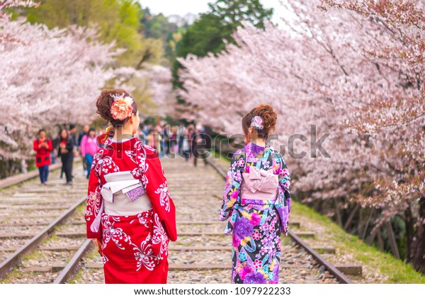 KYOTO, JAPAN - APRIL 5, 2016:  Cherry blossom festivals are an important custom. In this photo, several Japanese women in their traditional Kimono were enjoying the cherry blossoms at Keage Incline.