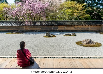 KYOTO, JAPAN - APRIL 8, 2013: Japanese tourist enjoys tranquility at Ryoanji Temple in Kyoto, Japan. This Zen Buddhist temple is famous for its rock garden.