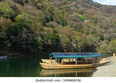 Kyoto, Japan - April 8, 2019 : Boats at Katsura river with mountain background in Arashiyama, Kyoto, Japan.