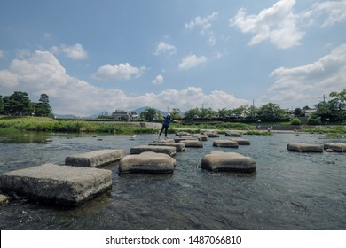Kyoto, Japan - August 09, 2019.A girl Stepping stones crossing Kamogawa river.Kyoto, Japan.