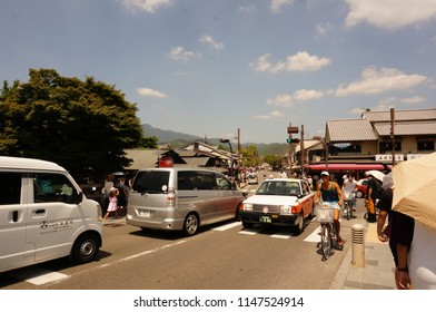 Kyoto / Japan - August 12, 2016: The view of traffic jam with many cars are on the street with big crosswalk and pedestrians walking pass many vintage buildings in Kyoto's Arashiyama district