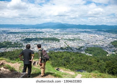KYOTO, JAPAN - AUGUST 21, 2016: Scenic view of Kyoto City seen from the peak of Daimonjiyama, with two Japanese men looking at Kyoto Imperial Palace, which is situated in a rectangular enclosure.