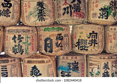 Kyoto / Japan - August 22, 2012: Traditional hand-painted barrels of Japanese rice wine lined and stacked. Sake casks