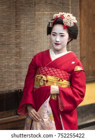 Kyoto, JAPAN - CIRCA September 2016: Young woman dressed as maiko (young geisha) posing in street of Kyoto.