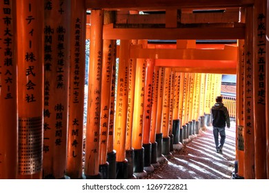 Kyoto, Japan - December 17. 2017: Man walking through the torii path (Senbon torii) at the Fushimi Inari-taisha, connecting the inner and outer shrines in Kyoto, Japan.