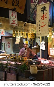 Kyoto, Japan - December 4, 2015: Various traditional Japanese food in Nishiki Market which is a five block long shopping street lined. Unidentified Japanese seller prepares chestnut for his customers.