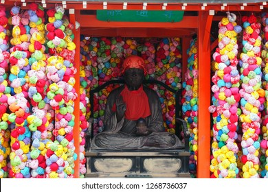 KYOTO, JAPAN -DECEMBER 5, 2018: Wooden sculpture depicting a guardian warrior with small color balls as sacrifices from prayers