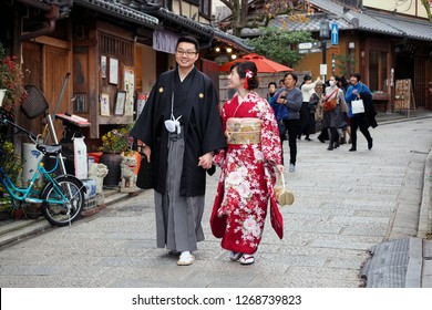 KYOTO, JAPAN -DECEMBER 5, 2018: Married couple walking on the shopping street in Traditional Japanese clothes