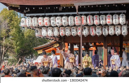 Kyoto, Japan - February 2, 2019: People dressed in traditional attire throw dried soybeans in Setsubun Festival at Yasaka Shrine.