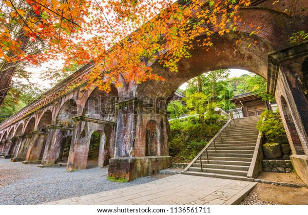 Kyoto, Japan at the historic Nanzenji Temple aqueduct behind autumn foliage.