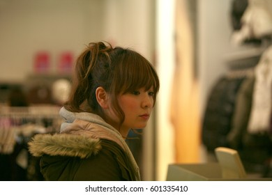 Kyoto, Japan - January 11, 2008: Japanese girl pays at the checkout in the clothing store on the Shijo Street - the nightlife center of Kyoto, next to the famous Gion district.