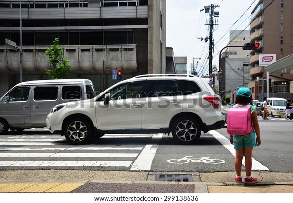 KYOTO, JAPAN - JULY 11 : Children japanese girl waiting cross over road at crosswalk traffic road near Gojo subway station on July 11, 2015 in Kyoto, Japan